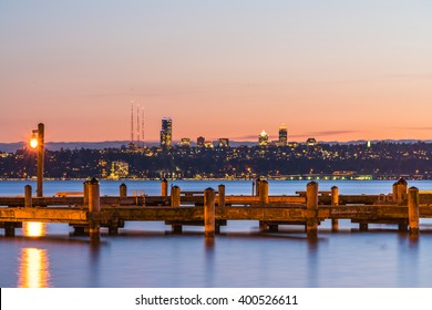dock with background of Bellevue cityscape with reflection on lake washington at night