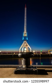 At the dock of the bay a high up crane against a blue starry sky and the red orange colors of the setting sun. Night photography in Harlingen harbor in the  along the Wadden Sea and the North Sea