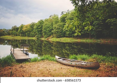 Dock and canoe on serene north woods lake. Forest reflection in calm water with hazy sky above.