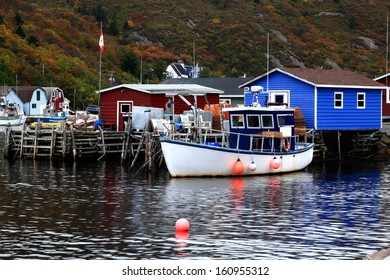 Dock for crab fishing boats, stocked on pile Crab Nets, bungalows for equipment in Petty Harbor, Newfoundland, Canada in fall season.