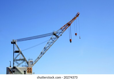 Dock crane at naval shipyard against blue sky