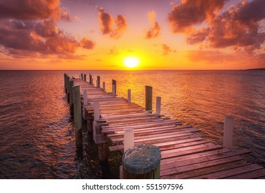 Dock during caribbean sunset, beautiful magenta colors and perspective of this boat dock and fishing dock in Eleuthera island, Bahamas