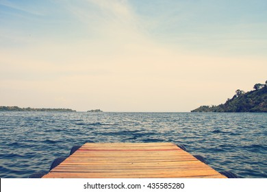 Dock extending out into beautiful blue water, vintage effect