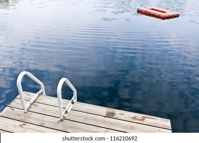 Dock and ladder on calm summer lake with diving platform in Ontario Canada