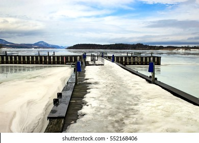 A dock and lake iced over in the winter