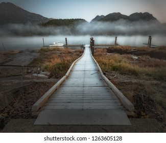 Dock leading to a foggy river with mountains along shore in Pitt Meadows.