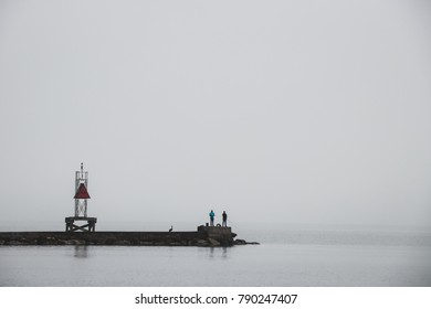 A dock leading to the ocean foggy