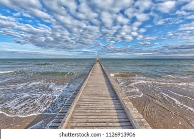 A dock leads to the mediterranean sea at the beach of Lido die Jesolo, Italy, with a gorgeous cloudy sky and beautiful blue-turquoise colors