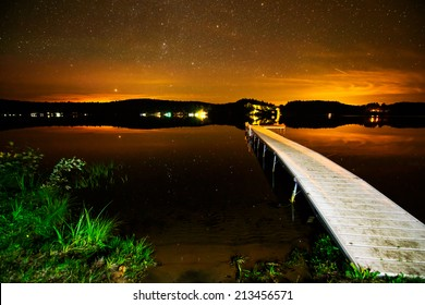 A dock on a lake under a starry sky after sunset.  Image contains some grain due to the high ISO and long exposure required for this type of photography.