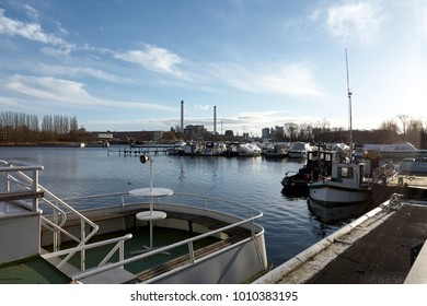 Dock on a River, under a Blue Cloudy Sky, on a mild Winter Morning, with Industry Buildings in the background