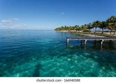 Dock on tropical island loaded with palm trees highlight pattern of sunlight in beautiful turquoise waters of the Caribbean