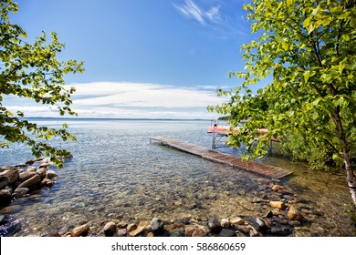 Dock and rocky beach on West Grand Traverse Bay and Lake Michigan on a sunny summer day in northern Michigan near Traverse City