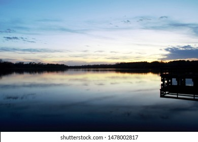 Dock silhouette at the lake during dusk.  Reflection of the sunset in the lake.