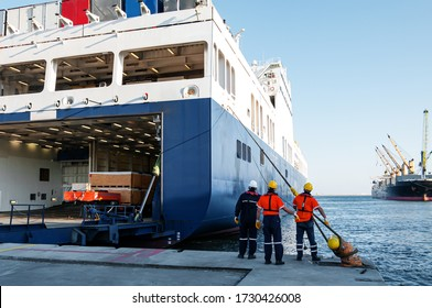 Dock workers pulling ship rope