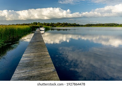 A docked boat at a wooden jetty. The blue sky, white clouds ans green plants reflect in the lake during a sunny day in the summer during the afternoon.