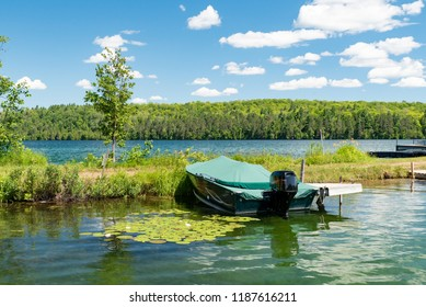 Docked motorboat on a lake next to lily pads in Ontario Canada's Cottage Country with clouds in a blue sky on a summer morning.