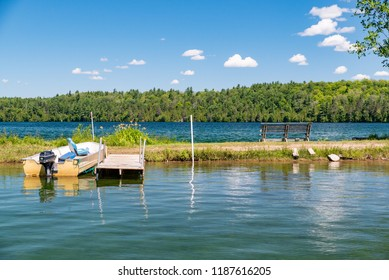 Docked motorboat on a lake in Ontario Canada's Cottage Country with flowers, park bench, and  clouds in a blue sky on a summer morning.