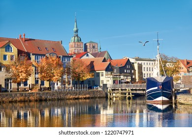 Docked sail boats and houses reflecting in channel with brick towers of Stralsund in Northern Germany