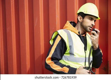 Docker guy in hard hat using walkie talkie, side view