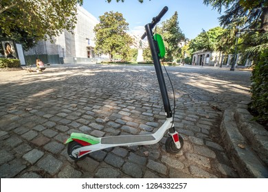 Dockless electric kick scooters from a scooter-sharing system parked on a sidewalk. One vehicule for rent at Madrid old town