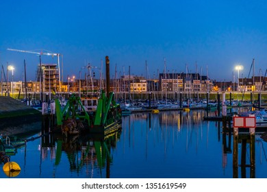 The docks of Blankenberge full with boats at night, city architecture of a popular town in Belgium
