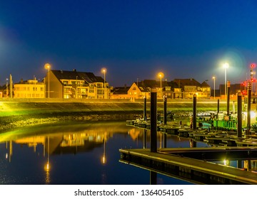 the docks of Blankenberge with view on the street and buildings, lighted city by night, Architecture of a popular city in Belgium