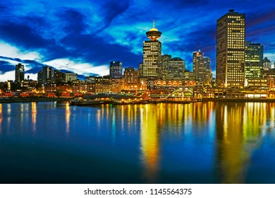 Docks of Downtown and Gas Town district of Vancouver on shoreline of Vancouver bay illuminated at dusk