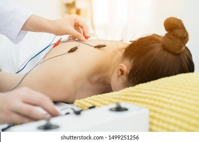 doctor or Acupuncturist applying electroacupuncture on patient's body. Shot of woman undergoing acupuncture treatment with electrical stimulator. meridian line. Traditional Chinese Medicine Concept