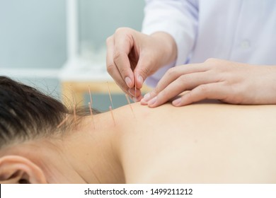 doctor or Acupuncturist inserting a needle into Asian female neck or back. patient having traditional Chinese treatment using acupuncture to restore an energy flow through specific points on the skin