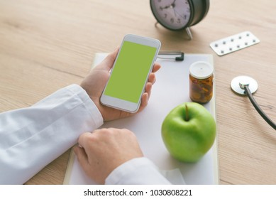 Doctor advising apple instead of pills and antibiotics, female hand in white coat holding samrtphone with blacnk mock up screen as copy space