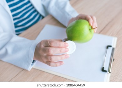 Doctor advising apple instead of pills and antibiotics, female hand in white coat holding green fruit as favorable way to achieve and maintain healthy lifestyle