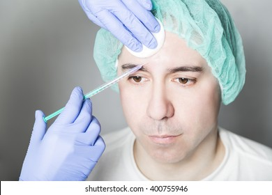 Doctor aesthetician makes hyaluronic acid beauty injections in the forehead of male patient in a medical cap and white t-shirt