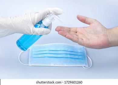 Ärzte Alkohol Gel sanitazer flüssige Reinigung Hände zu Menschen auf blauem Hintergrund für die Verhinderung von Corona Virus covid-19 , chirurgische Maske.  Konzept: Medizin und Gesundheitswesen, Menschen