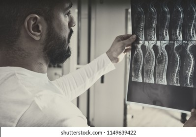 Doctor analysing X-ray image of human spine in consulting room