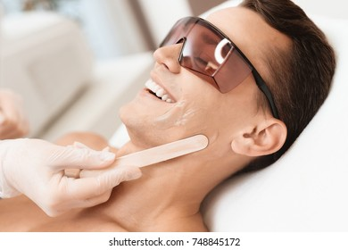 The doctor applies an epilation gel on the man's face. The man laughs, because he is ticklish. He lies on a couch in a modern beauty salon.