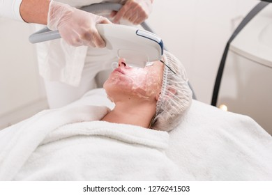 The doctor applies a special gel to the patient. Anti acne phototherapy with professional equipment. Beautiful woman during photo rejuvenation procedure. Face skin treatment at cosmetic clinic.