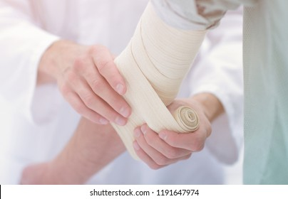 doctor applying elastic bandage on the elbow of the patient.