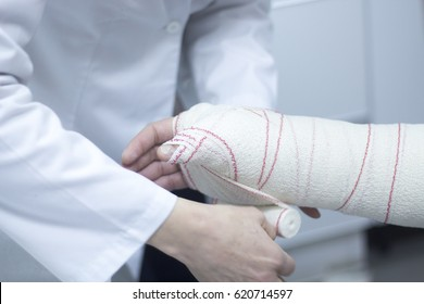 Doctor applying a plaster cast and bandages to patient forearm and wrist to immobilize after fracture injury.