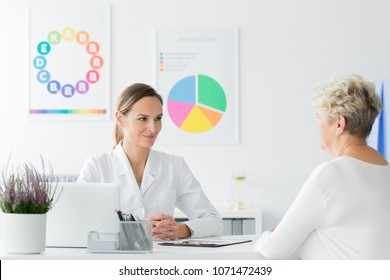 Doctor at an appointment looking happy with her elderly patient's weight loss progress