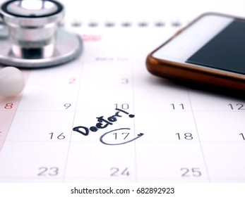 doctor appointment reminder on calendar with mobile phone; medical concept.