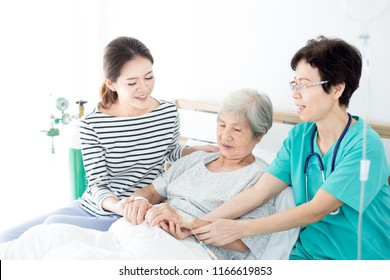 doctor and Asian female talk with old asian patient about disease symptom , elderly health care , palliative care, they  holding hand of patient, mother day
