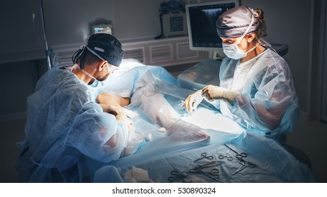 doctor and an assistant in the operating room for surgical venous vascular surgery clinic