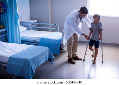Doctor assisting injured boy to walk with crutches in hospital