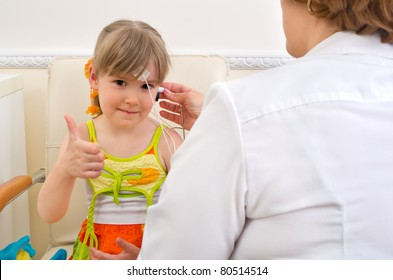 Doctor audiologist testing girl's ears on medical equipment