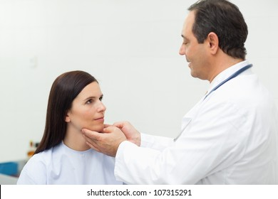 Doctor auscultating the neck of a patient in an examination room