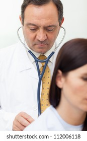 Doctor auscultating a patient in an examination