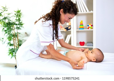Doctor and baby playing motoric games including arm spreading of a little baby