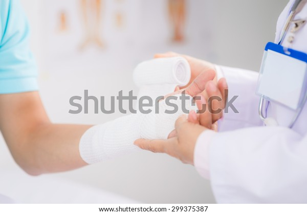 Doctor bandaging wrist of male patient with white bandage