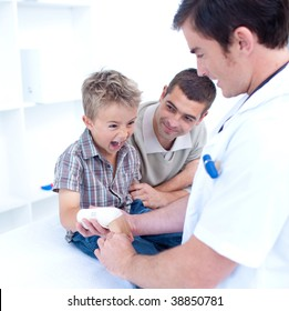 Doctor bandagins a patient's arm who is yelling in hospital