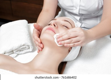 doctor beautician cleanses the skin woman with a sponge. Perfect cleaning - spa treatment skincare face.